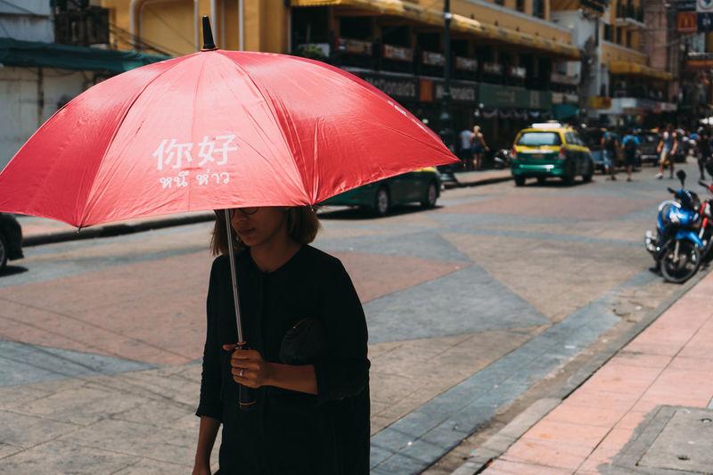 Woman standing on wet street in rain