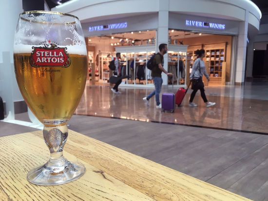 Brussels, Belgium - 15 August 2017: Chalice of Stella Artois sitting on a light colored wood table in the Brussels airport (BRU) in Brussels Belgium. Glass of Stella beer on a wood table in an airport Brussels Brussels Airport Stella Artois Stella ❤ Brussels Belgium Stella Stellaartois