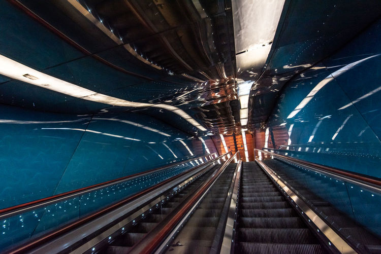 Low angle view of empty escalators with reflection at subway station