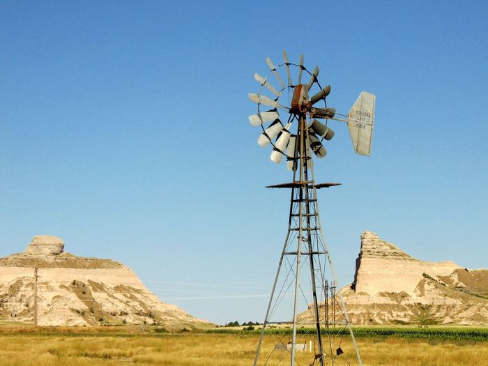 American-Style Windmill On Field Against Clear Blue Sky