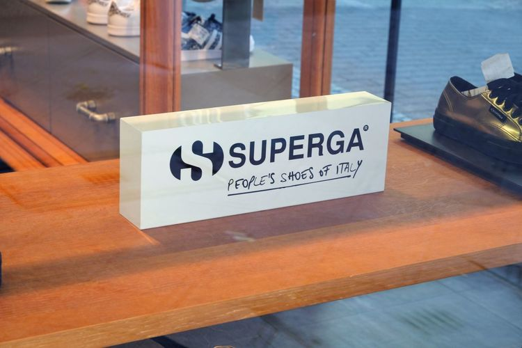 """Superga banner in shop window. Superga is an Italian brand of shoes founded in 1911. It originally made tennis shoes, including the famous model """"2750 Classic"""" Boutique Fashion Shoe Shoe Store Shoes Shop Shoes ♥ Superga Close-up Influencer No People Retail  Shoes Shoes Store Shop Shop Window Sign Store"""