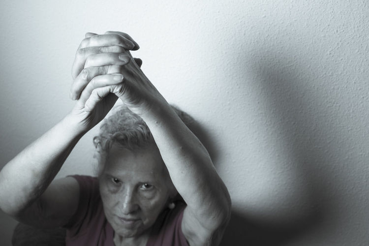Portrait Of Senior Woman With Hands Clasped Against Wall