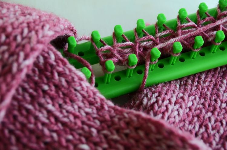 Long loom knifty knitter pattern. Close-up Detail Focus On Foreground Green Color Knitter Multi Colored Pink Color Selective Focus Sharp Yarn