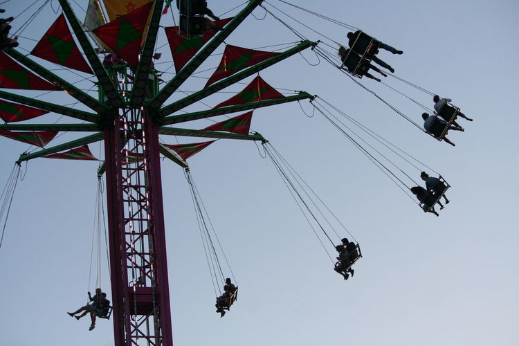 Low angle view of people on chain swing ride against clear sky
