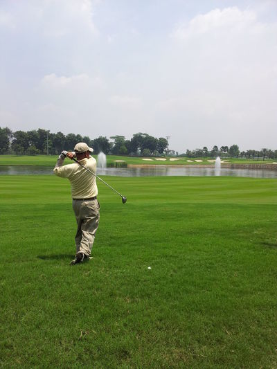 Man playing with golf on course against sky