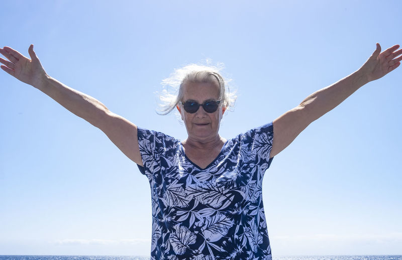 Portrait of woman wearing sunglasses standing against clear sky