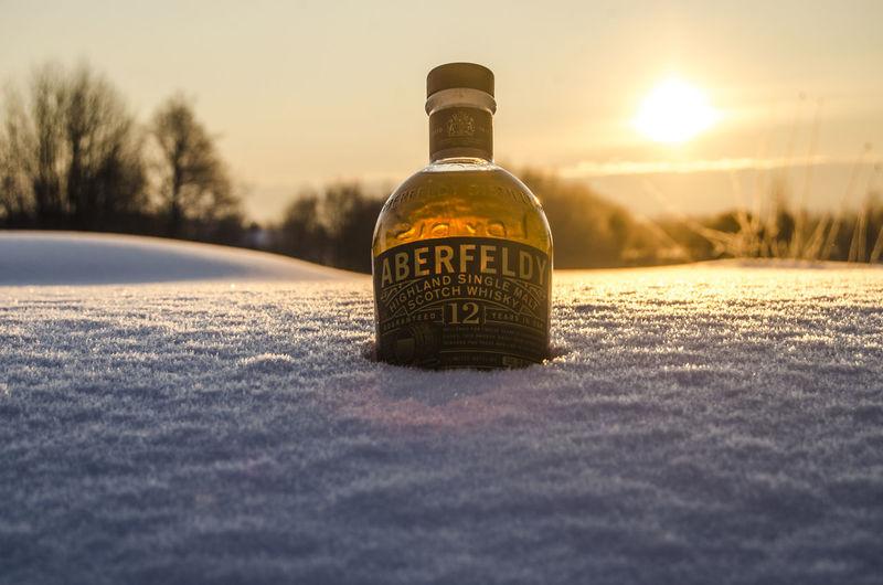 Close-up of bottle bottles against sunset sky