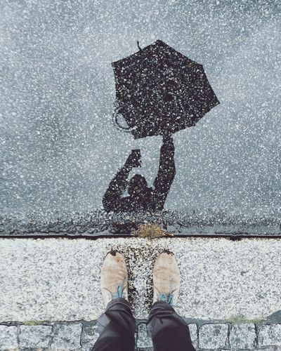 Low Section Of Person With Reflection On Street In Rainy Season