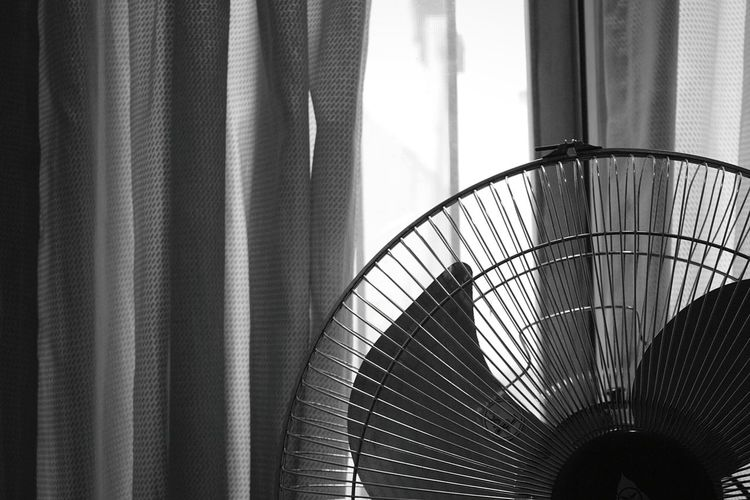 Close-up of cropped electric fan against curtained window