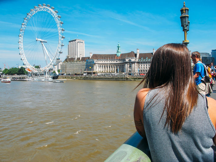 Girl looking out over London with view of London Eye London London Eye River Thames View Architecture Building Exterior Built Structure City Day Girl Landmark Leisure Activity Lifestyles One Person Outdoors Real People Rear View River Sky Tourism Travel Travel Destinations Water Women Young Women