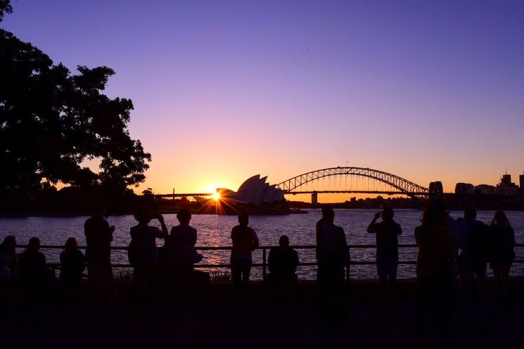 Rear View Of Silhouette People Looking At Sydney Opera House And Bridge