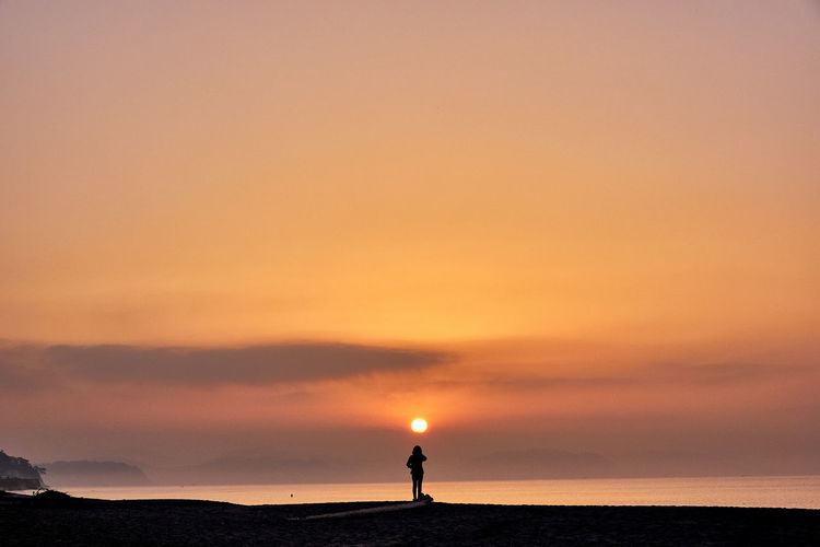 Silhouette woman standing by sea against sky during sunrise