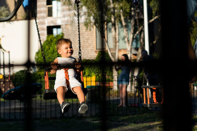 Baby boy in the playground Boys Child Childhood Full Length Innocence Leisure Activity Males  One Person Outdoors Playground Real People Sitting Swing