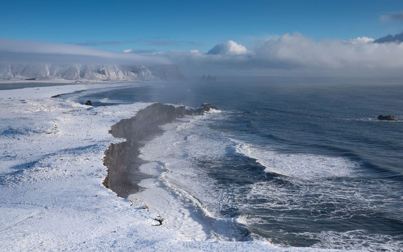 Panoramic image of the coastal landscape of Cape Dyrholaey on a winter day with snow-covered coastline, Iceland Water Scenics - Nature Sea Beauty In Nature Sky Nature Day Dyrhólaey Cape Dyrholaey Iceland Travel Travel Destinations Tourism Landscape Nature Scenics Scenery Coast Coastline Coastal Feature Winter Wintertime Snow Panorama Ocean Beach Cliff Environment Ecosystem  Outdoors No People Europe