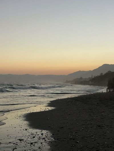 EyeEm Selects Sea Beach Sunset Beauty In Nature Nature Scenics Water Shore Sand Tranquil Scene Tranquility Mountain Outdoors Silhouette Sky Wave No People Mountain Range Clear Sky Travel Destinations Marbella