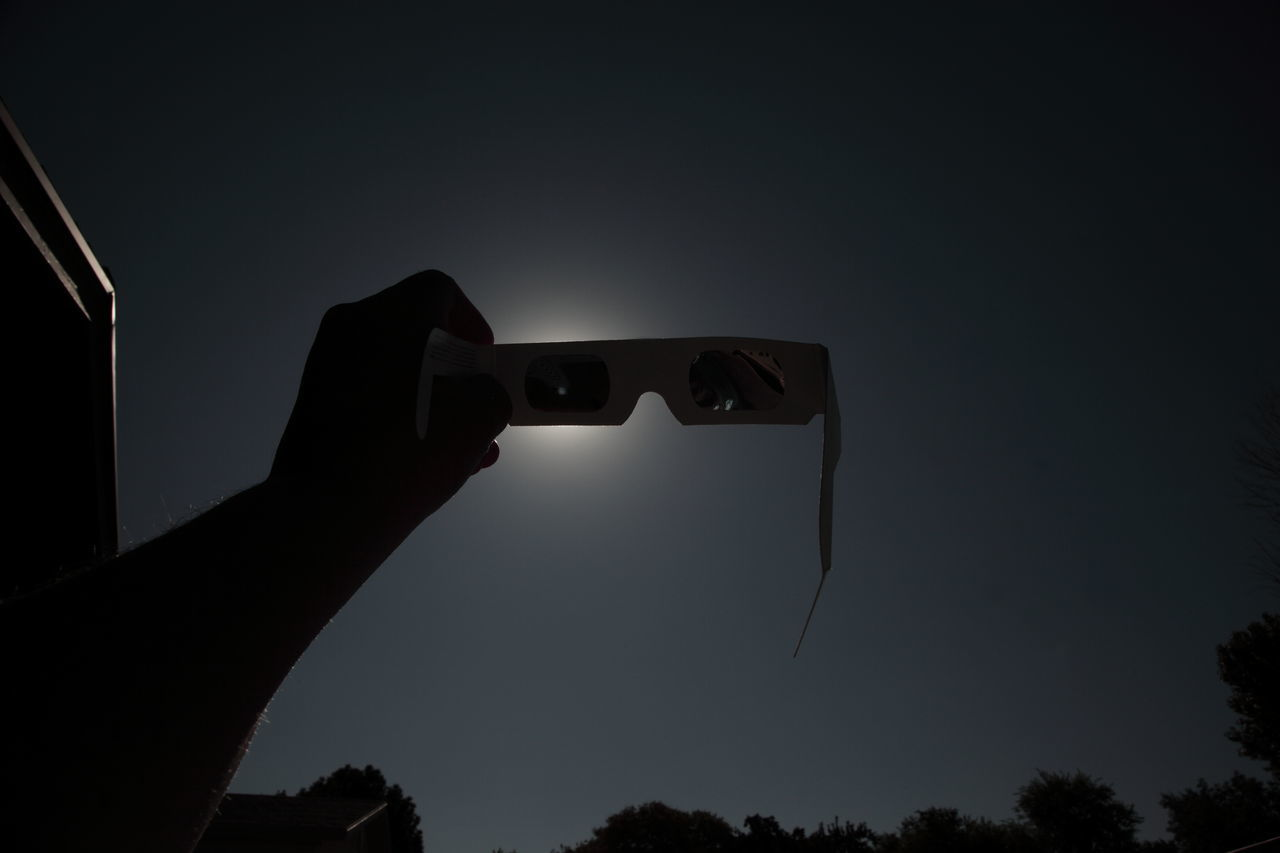 Close-Up Of Hand Holding 3-D Glasses Against Sky