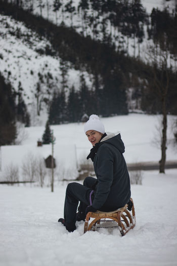 Man sitting on snow covered field