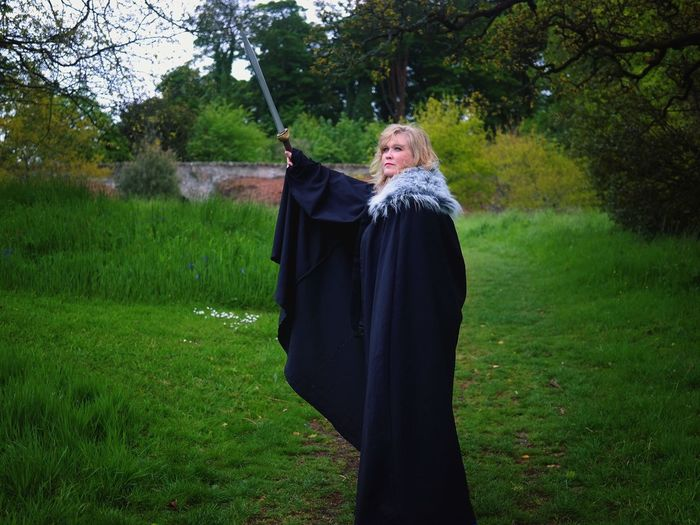 Mid Adult Woman In Black Costume While Raising Sword In Grass