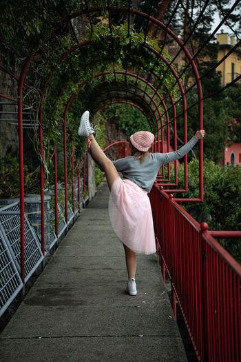 Rear view of woman standing on footbridge