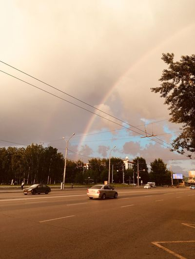Cars on road against rainbow in city