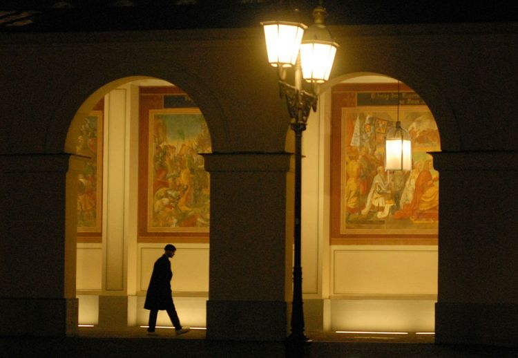 Silhouette man standing by illuminated building at night