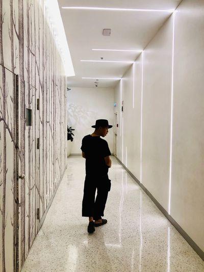 Rear view of boy walking in corridor of building
