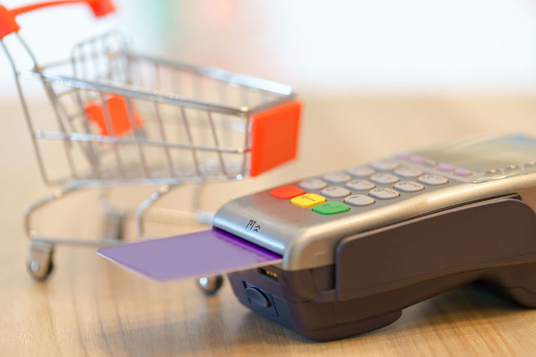 Close-up of credit card with machinery and miniature shopping cart on table