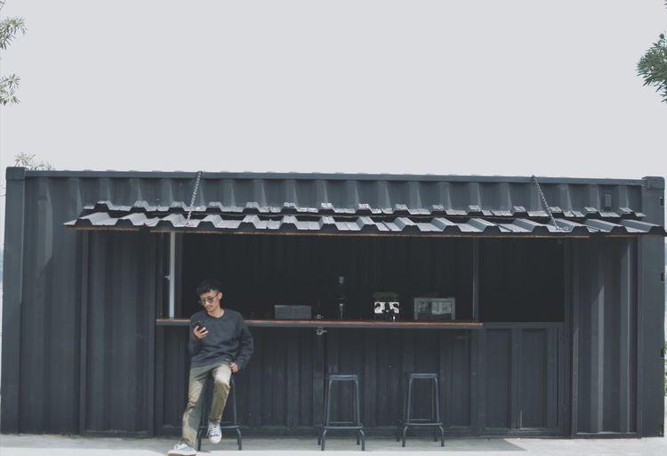 Full length portrait of man standing against building