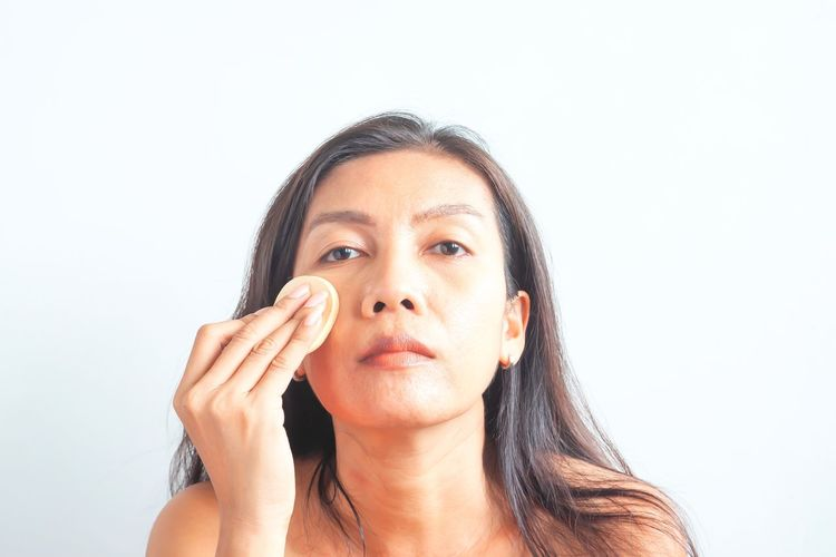 Asian woman applying foundation powder on face, skin problem. Beauty and Health Human Face Beautiful Woman Hairstyle Young Adult Hair Looking Mature Adult Close-up Cut Out Looking Up Adult Women Indoors  White Background Looking At Camera Copy Space Front View One Person Studio Shot Portrait Headshot Aged Aged Beauty Diversity Imperfection Routines Everyday Ethnicity ASIA Asian  Non-binary Makeup Representation 40+ Acne Pimples Problem Skin