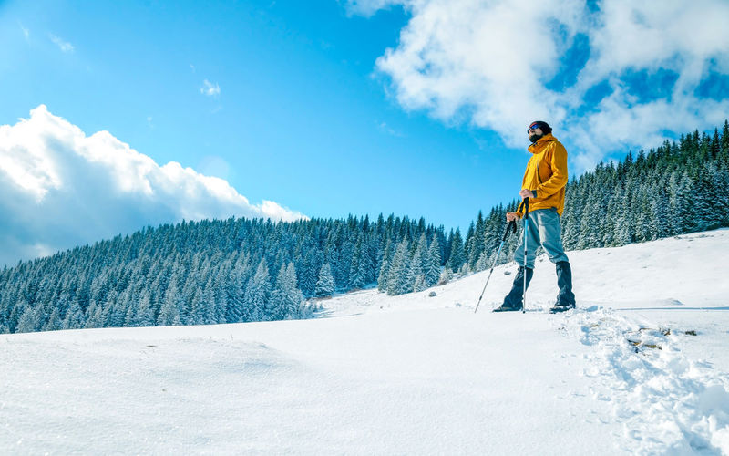 Full length of man standing on snow covered mountain
