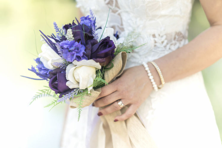 Midsection Of Bride Holding Flower Bouquet During Wedding Ceremony