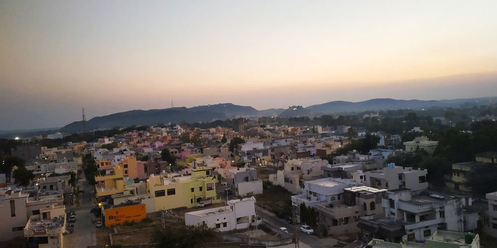 a picture of hills from a hill in between which are so many houses in the city of hills . #hills Hillcity Mobilephotography Dungarpur Rajasthan India Sunset Mountain Downtown District TOWNSCAPE