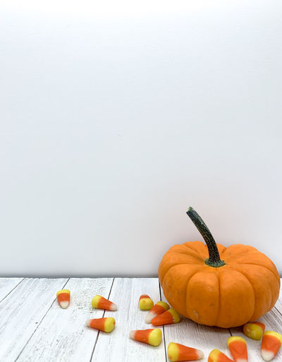 Close-up of pumpkin on table against wall
