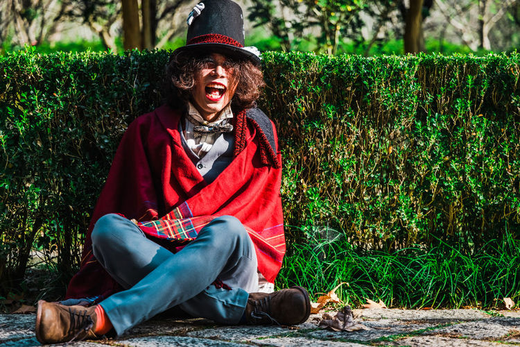 Man cosplaying mad hatter sitting on ground against hedges