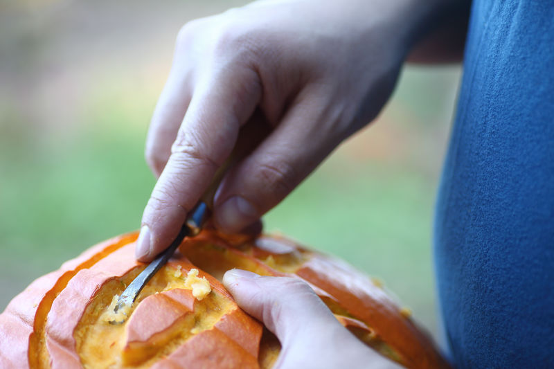 American Culture Autumn Carving Carving Tool Close-up Craft Fall Fingers Halloween Hands Holding Holiday Tradition Man Natural Light October Outdoors Part Of Pumpkin Seasonal Textures Using Tool Vibrant Color