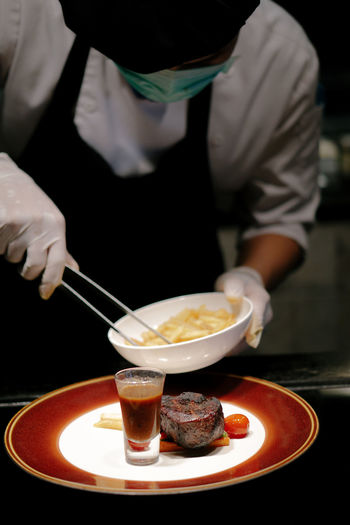 Close-up of chef arranging food in plate at restaurant