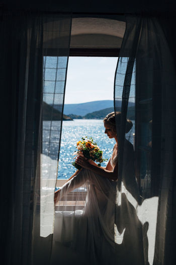 Woman with flower bouquet sitting on window at home
