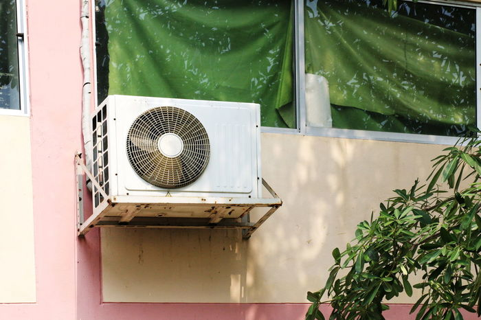 old Air conditioner mounted outside the building office Air Conditioners Air Conditioner Air Conditioner Ventilators Office Air Conditioner Holes Air Conditioner Units Air Duct Architecture Building Building Office Close-up Day Electric Fan Exhaust Fan Fan Green Color Old Outdoors Outside Plant Plant Part Potted Plant Technology Wall - Building Feature Window