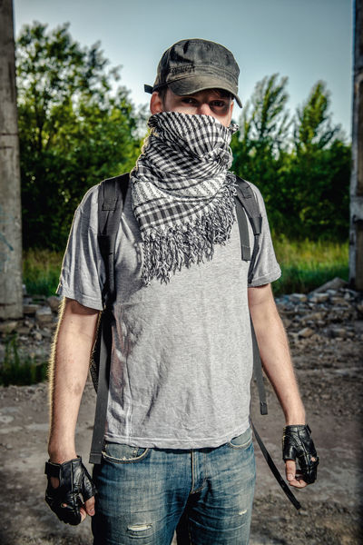 Man covering face with a scarf. Terrorism concept. Adult Aggression  Destruction Disguise Man Mess OutLaw Aggressive Caucasian Disturbance Hide Hooligan Human Male One Person Outdoors People Person Rebel Riot Terrorism Terrorist Vandalism War Young Adult