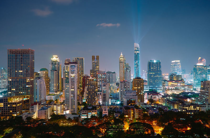 Modern buildings in city against sky during dusk