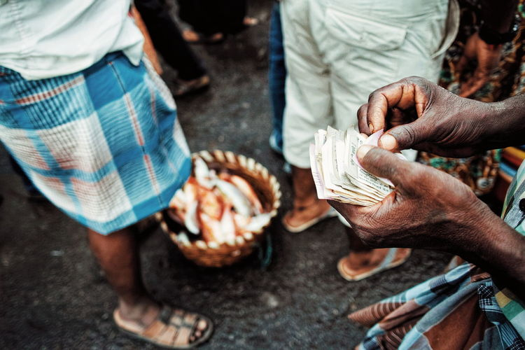 Low section of vendor holding currency