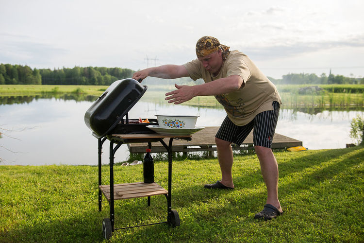 Young man grilling by lake against sky