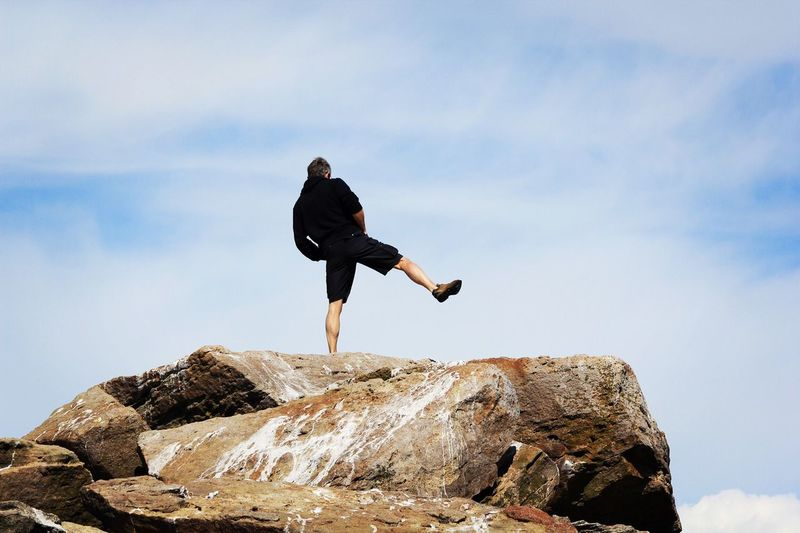 Rear view of man standing on one leg at rock against sky