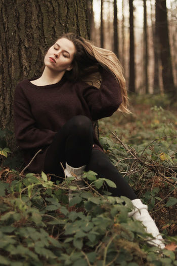 Portrait of woman with closed eyes sitting in the forest