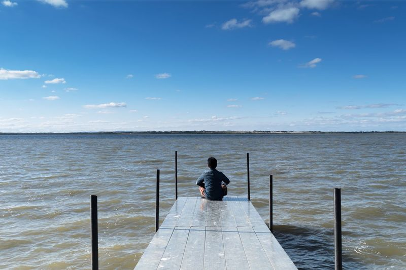 Rear View Of Man Sitting On Pier By River Against Blue Sky During Sunny Day