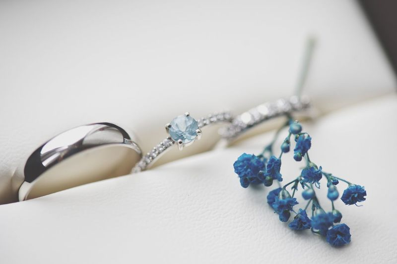Close-up of wedding rings with artificial flower in box