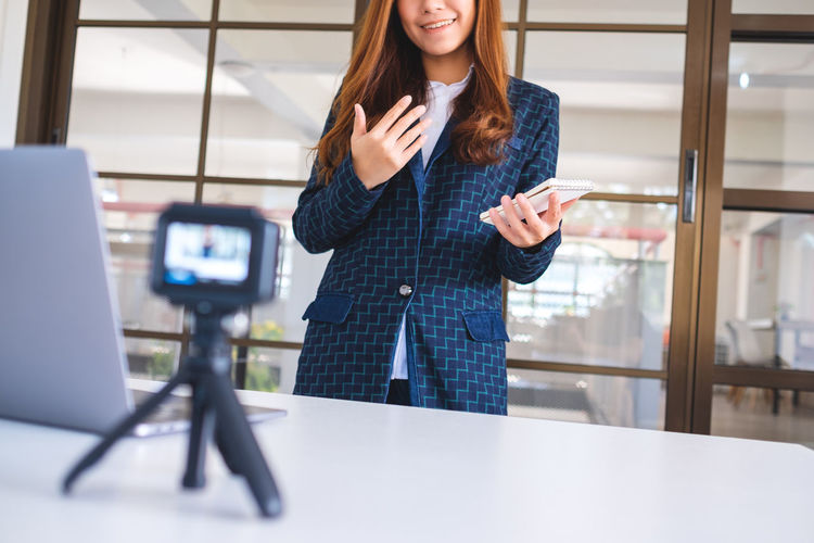 Midsection of businesswoman filming presentation in office