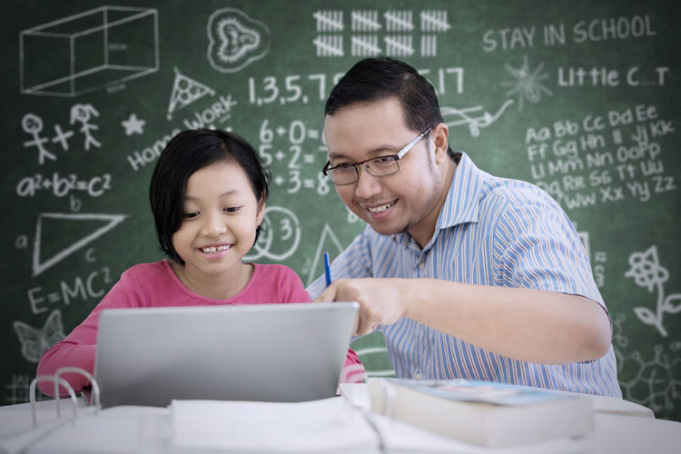 Adult Blackboard  Board Communication Connection Emotion Front View Happiness Indoors  Men Positive Emotion Smiling Technology Togetherness Two People Using Laptop Wireless Technology Women