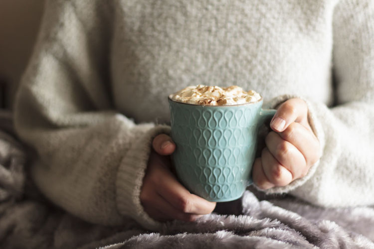 Woman covered with blanket holding mug of hot drink with whipped cream