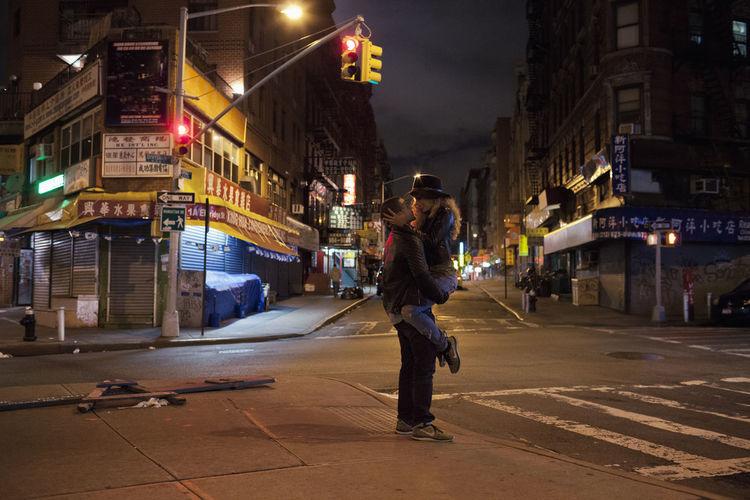 Full length of man walking on illuminated street at night